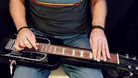 A Man Playing A Lap Steel Guitar
